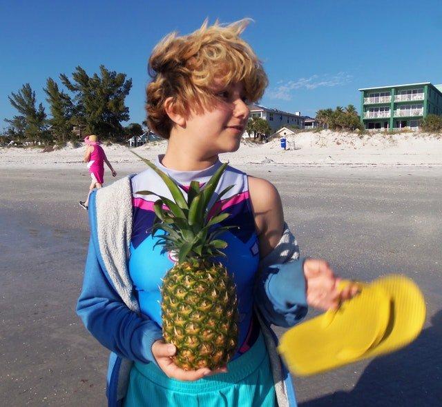 mujer con piña en la playa