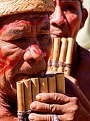 chaman del amazonas tocando intrumento musical flauta